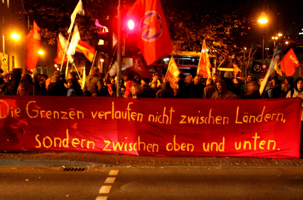 Demonstranten mit Fahnen und Transparent: Die Grenzen verlaufen nicht zwischen Lndern, sondern zwischen oben und unten.