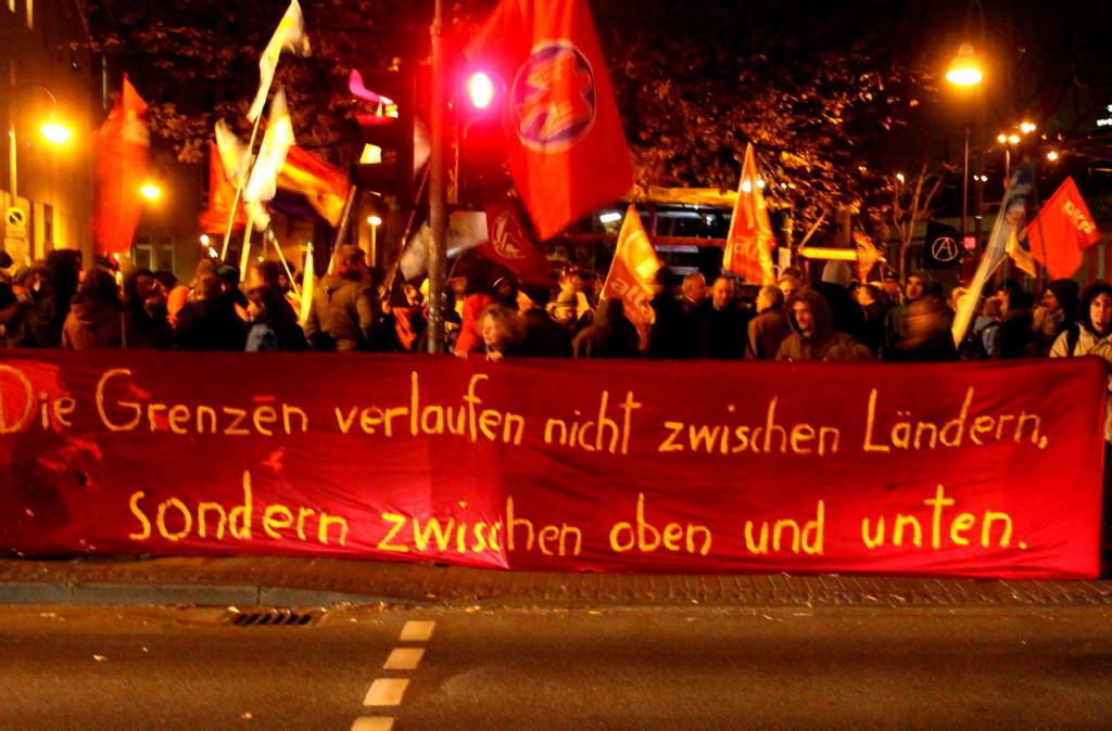 Demonstranten mit Fahnen und Transparent: »Die Grenzen verlaufen nicht zwischen Ländern, sondern zwischen oben und unten«.